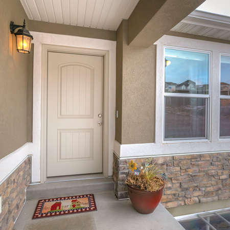 Square White front door and reflective window of a home against road and cloudy sky. A colorful doormat, potted plant, and wall lamp adorns this home's entryway.