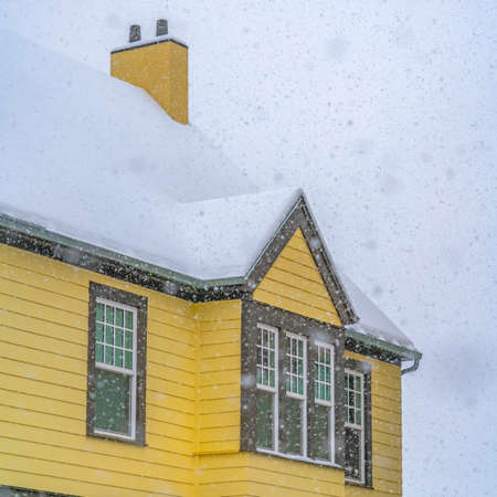 Snow falling on a yellow home in Daybreak Utah. Frosty snow falling on a yellow home in Daybreak, Utah during winter season, The homes roof is covered with a thick sheet of fresh snow.