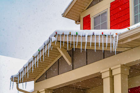 Home in Daybreak Utah with cloudy sky background viewed in winter. The falling snow accumulates on the roof with icicles and colorful lights. Stock Photo