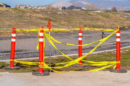 Orange traffic poles with yellow caution tape surrounding a hole on the ground. Railroad track, homes, mountain and sky can be seen in the background.