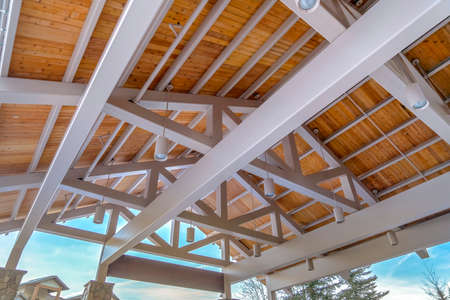 Roof of a pavilion seen from the inside against trees and cloudy blue sky. Cylindrical lights are hanging on the wooden planks of the roof supported by a white framework.