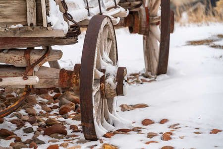 Close up of the rusty wheels of an old wooden wagon viewed in winter. The wagon and the rocky terrain is blanketed with powdery white snow.