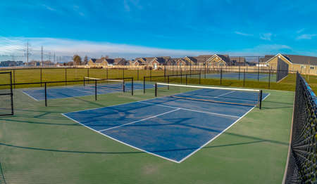 Tennis courts on a wide lush lawn underneath a vivid blue sky with clouds. Scenic view on a sunny day with charming homes and mountain in the background.