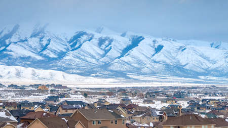 Panorama Homes with a snowy mountain and cloudy sky background viewed in winter. The scenic town is coated with fresh powdery snow on this frosty season. Фото со стока