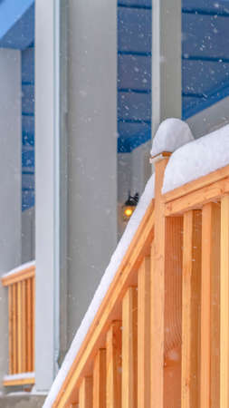 Winter view of the stairs leading to the front porch of a home with balcony. The railing of the wooden stairs are topped with frosty snow in December.