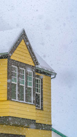 Vertical Snowy yellow home viewed through falling snow. Exterior of a yellow home in Daybreak, Utah with snow covered roof viewed through falling snow during a frosty winter day in December.