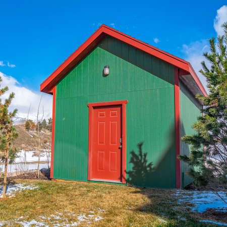 Clear Square Small storage shed on grassy terrain with trees and powdery snow. A vibrant blue sky with fluffy white clouds can be seen in the background on this sunny winter day.