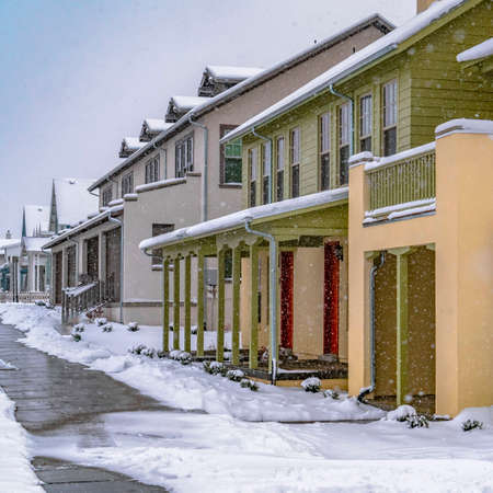 Square Pathway in front of cozy homes in Daybreak Utah viewed in winter. The snow falling from the cloudy sky creates a blanket of frost on the landscape.