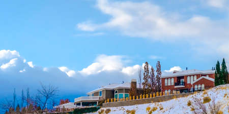 Homes on snowy hill against sky with puffy clouds. Scenic snow covered landscape in Salt Lake City during winter season. Lovely homes sits on top of a snowy hill against blue sky with puffy clouds.