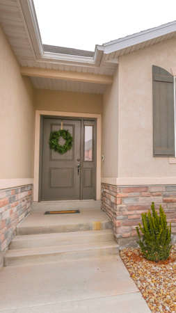 Vertical Pathway and stairs leading to the gray front door with wreath and sidelight. Plants are planted on the landscaped yard covered with small rocks.