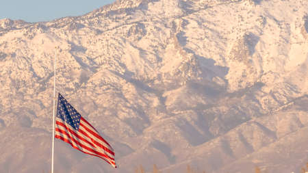 Panorama American flag and building with Mount Timpanogos and sky in the background. The majestic mountain is capped with snow on this sunny winter day in Eagle Mountain, Utah. Reklamní fotografie