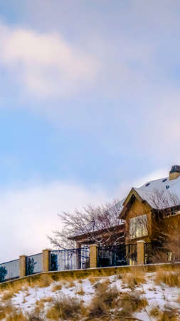 Clear Vertical Salt Lake City home on a snowy hill against sky. Picturesque landscape in Salt Lake City with a home sitting on top of a snow covered hill beneath a striking blue sky with puffy clouds in winter.