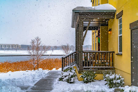 Entrance of a home in Daybreak Utah with lake and buildings in the background. The path on the snowy yard leads to the stairs and porch of the house.