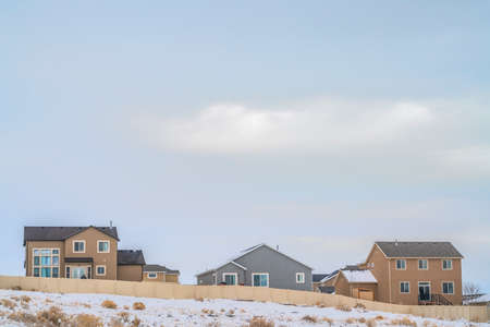 Facade of houses with a boundless cloudy sky background in winter. A terrain coated with fresh powdery snow cna be seen in front of the wooden fence.