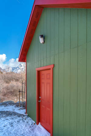 Storage shed against trees and snow capped mountain under cloudy blue sky. The ground outside the shed is dusted with snow on this sunny winter day.