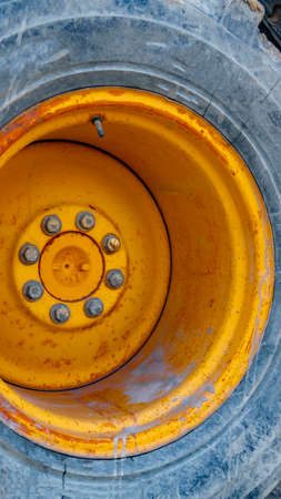 Clear Vertical Close up of the wheel of a yellow loader parked on the road on a sunny day. The construction machinery has a metal rim with rust and peeling paint. Reklamní fotografie
