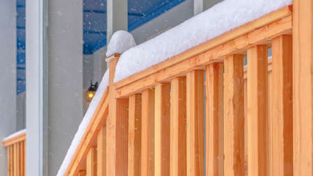 Clear Panorama Winter view of the stairs leading to the front porch of a home with balcony. The railing of the wooden stairs are topped with frosty snow in December.