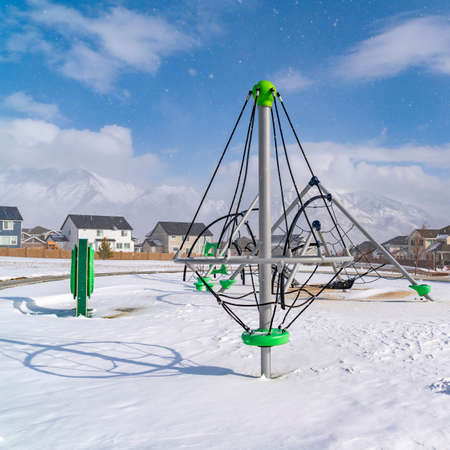 Square Playground and homes on a frosted neighborhood on a sunny winter day. A mountain covered with snow and sky with puffy clouds can be seen in the scenic distance.
