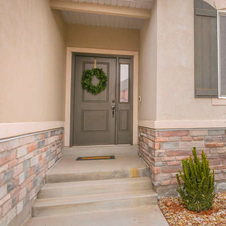 Clear Square Pathway and stairs leading to the gray front door with wreath and sidelight. Plants are planted on the landscaped yard covered with small rocks.