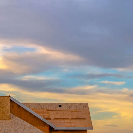 Clear Square Close up of the roof of a new home viewed at a construction site at sunset. A pale blue sky filled with thick clouds can be seen over the unfinished roof. 스톡 콘텐츠