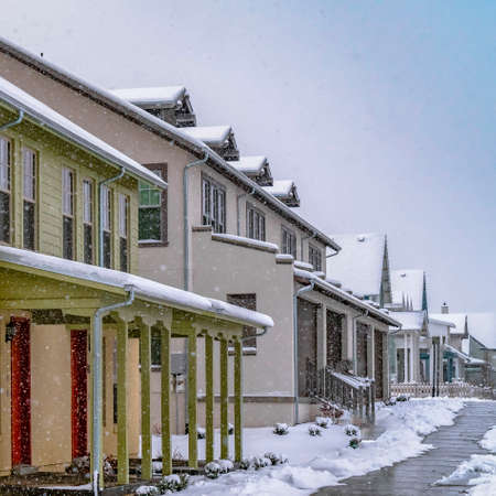 Clear Square Pathway in front of cozy homes in Daybreak Utah viewed in winter. The snow falling from the cloudy sky creates a blanket of frost on the landscape.