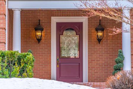 Entrada de una casa con una hermosa puerta de entrada y un patio cubierto de nieve en invierno. La puerta con un panel de vidrio decorativo se encuentra entre las lámparas montadas en la pared exterior de ladrillo rojo.