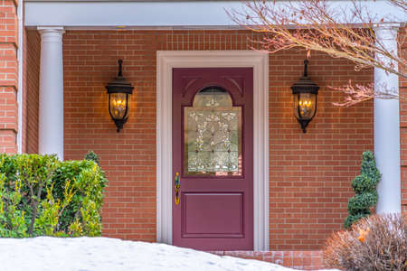 Entrance of a home with a beautiful front door and snowy yard in winter. The door with a decorative glass panel is between lamps mounted on the exterior red brick wall.