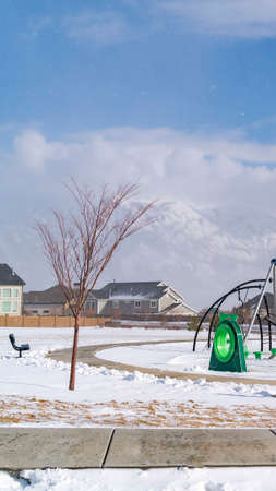 Vertical Playground and bench on a snowy playground against homes in winter. A snow covered mountain and bluw sky with clouds can be seen in the distance. Фото со стока - 122767348