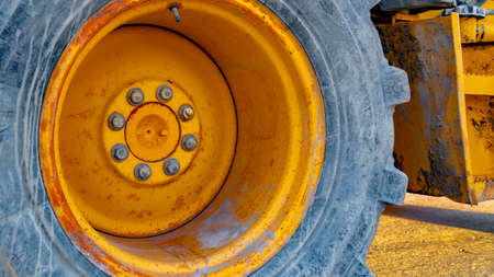 Panorama Close up of the wheel of a yellow loader parked on the road on a sunny day. The construction machinery has a metal rim with rust and peeling paint.