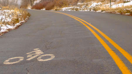 Panorama Winter road with bicycle lane sign on the surface. Road on a snowy mountain against sky in Salt Lake City. A white bicycle lane symbol is painted on the surface of the curving mountain road.