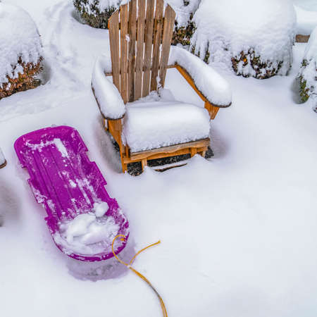 Clear Square Wooden chairs and purple sled against powdery white snow in Daybreak Utah. Behind the chairs are round shrubs capped with snow during winter season.