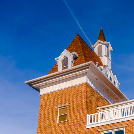 Clear Square Exterior view of a building against vibrant blue sky on a bright sunny day. A contrail can also be seen behind the sunlit roof and steeple of the building.