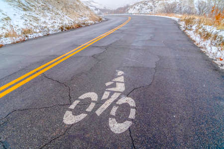 Weathered mountain road with bicycle lane sign. Weathered road curving along a snow covered mountain in winter. A white bicycle lane sign is painted on the roads cracked and rough surface.