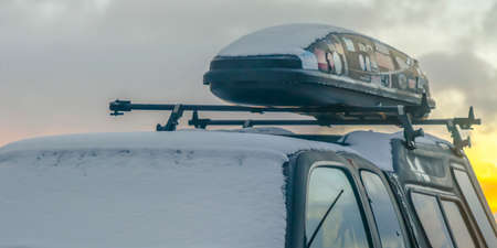 Black vehicle with roof rack and car top carrier covered with snow in winter. A cloudy sky with a golden glow can be seen in the background at sunset.