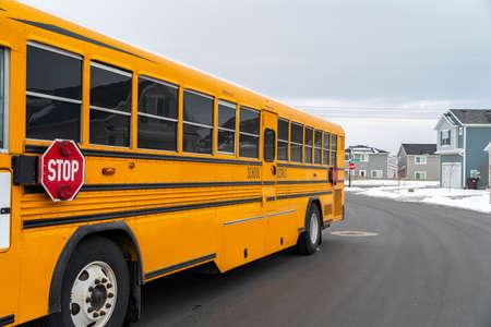 Vista laterale di uno scuolabus su una strada che passa attraverso case innevate in inverno. Finestre riflettenti e segnale di stop con luci di segnalazione sono visibili all'esterno dell'autobus.