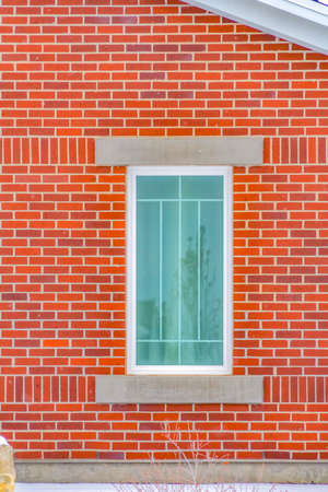 Close up of the rectangular window of a building with red brick wall. Reflection of a building, tree, and sky can be seen on the glass window.