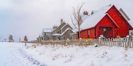 Winter weather with trail stamped on the snow towards the houses in Daybreak. The charming homes have snowy roofs and white picket fences.