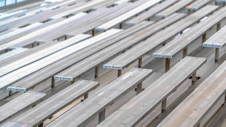 Clear Panorama Close up of tiered rows of benches at a sports field viewed on a sunny day. Seating numbers can be seen on the surface of the raised bleachers.