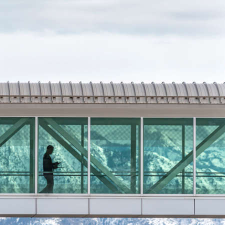 Clear Square Skyway connecting buildings with a snowy mountain and cloudy sky background. Silhouette of a man walking inside the passage ay can be seen through the clear glass wall. Stock Photo