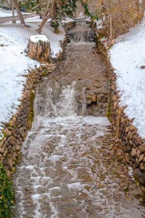 Stone lined creek with shallow and clear running water in Salt lake City