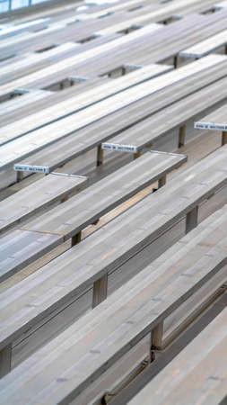 Vertical Close up of tiered rows of benches at a sports field viewed on a sunny day.
