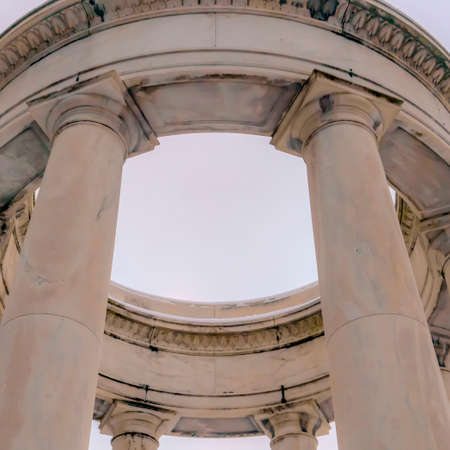 Square Looking up at a white circular structure supported by smooth columns Stock Photo