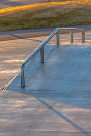 lose up of an inclined concrete ramp at a park lit by sunlight on a sunny day