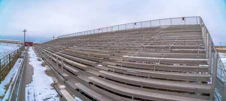 Row of tiered benches on a sports arena under a cloudy sky in winter