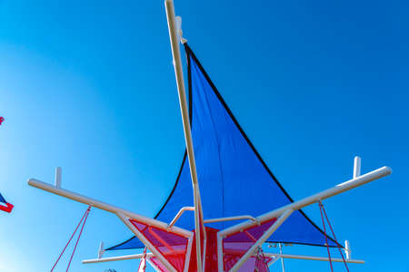 Thin triangular blue roof supported by smooth white poles against clear sky Stock Photo
