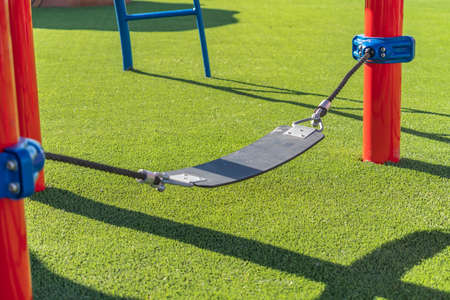 Play area with a seat supported by ropes that are connected to red poles