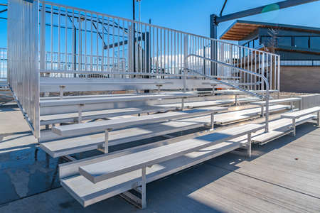 Bleachers with railings against a building and cloudy blue sky