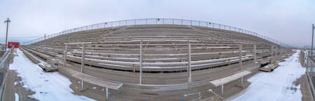 Tiered seating at a sports arena under a cloud filled sky in winter
