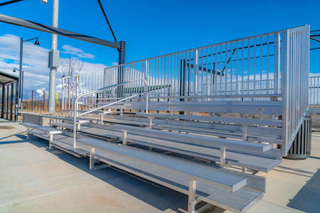 Raised tiered rows of benches with railings at a sports filed on a sunny day