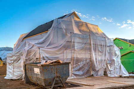 Plastic sheet covering an unfinished house and scaffoldings against blue sky